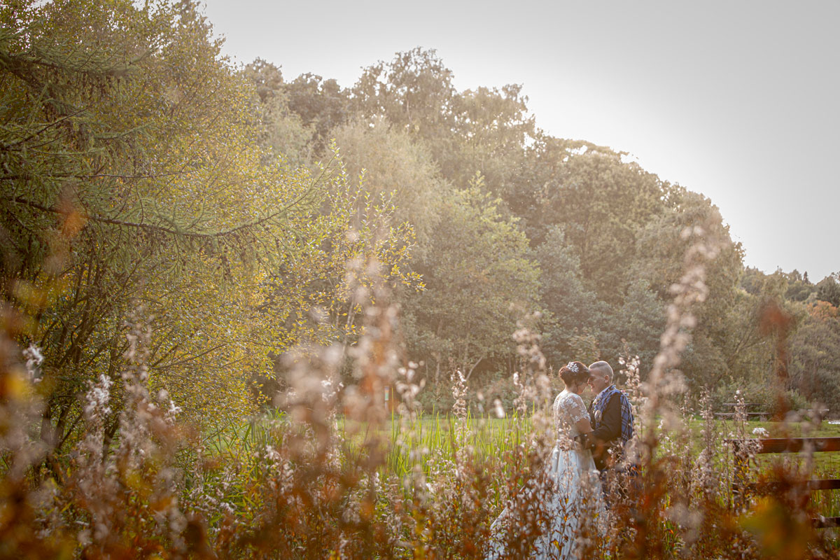 groom kissing bride on forehead in field with flowers in foreground