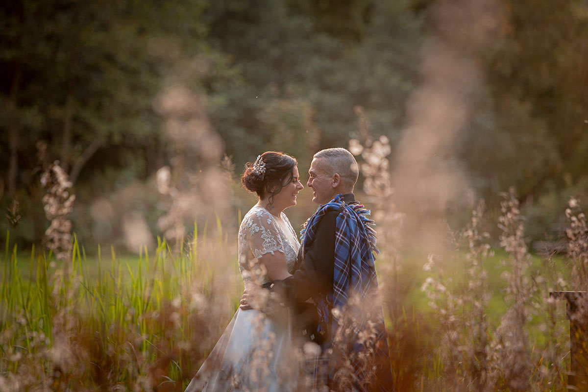 bride and groom in field smiling face to face