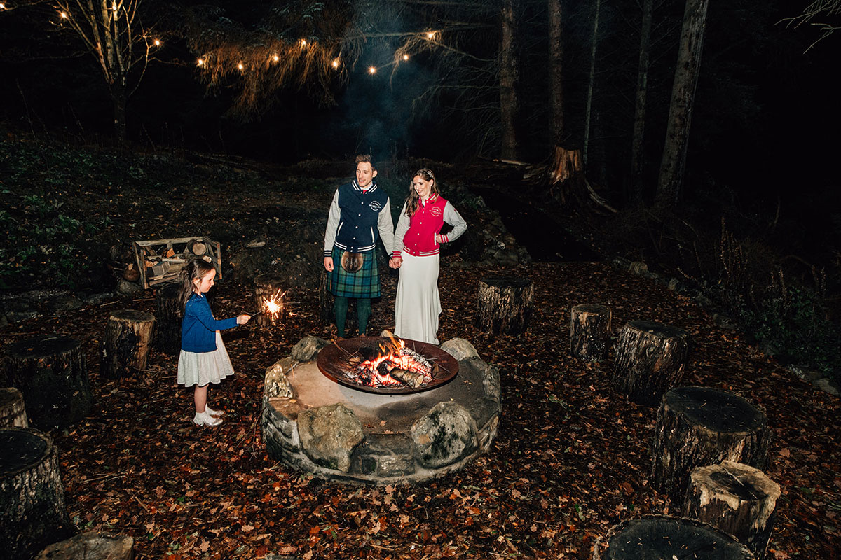 bride and groom wearing his and her wedding bomber jackets standing by fire pit at Cardney Steading with young girl wedding guest playing with sparkler