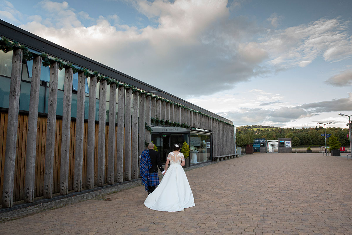 bride and groom walking towards The Shore Loch Lomond