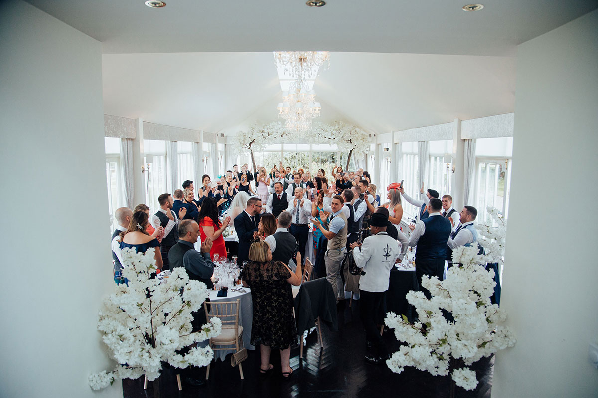permanent marquee at Carlowrie Castle filled with cheering wedding guests as bride and groom arrive