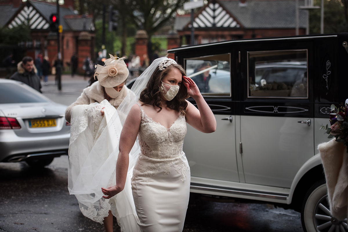 bride wearing mask with train carried by mum outside Oran Mor