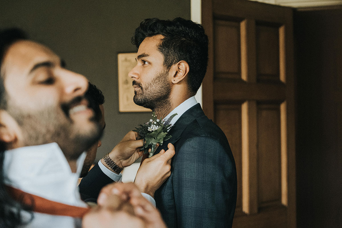 profile of groom getting ready on wedding morning with male guest pinning on buttonhole and guest tying tie in foreground