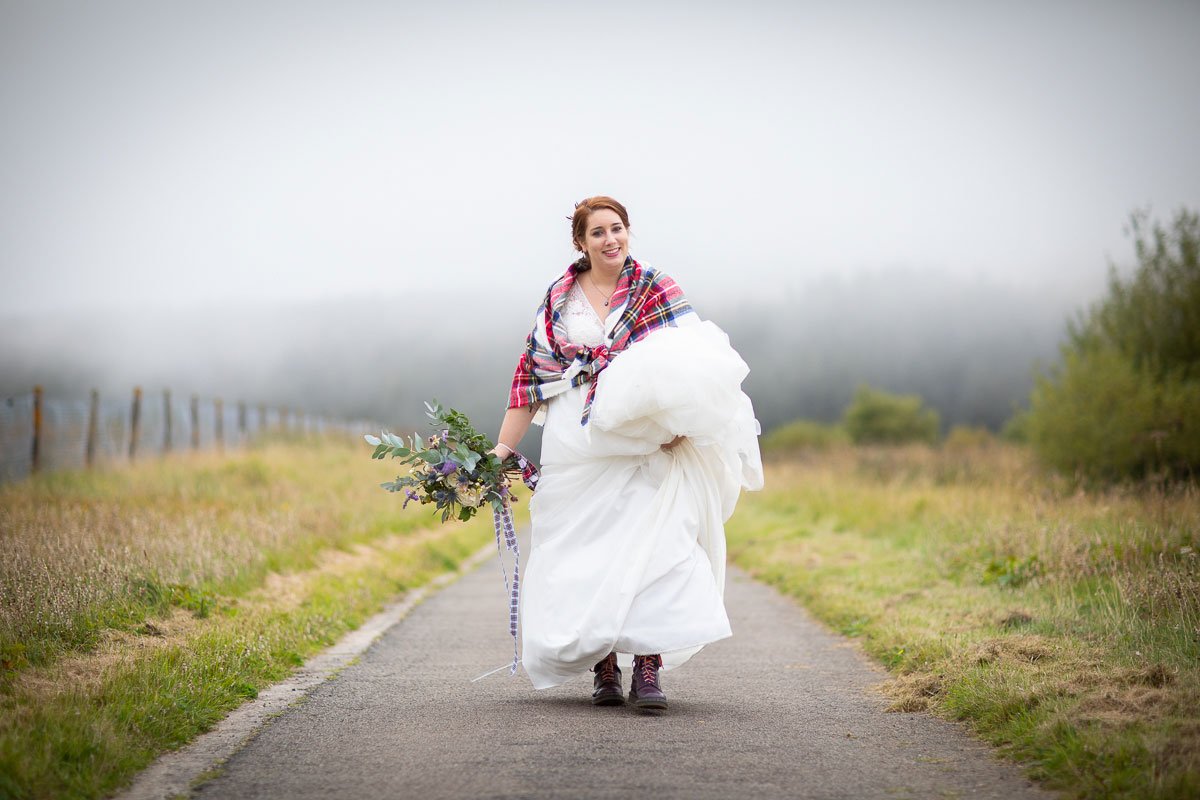 bride wearing tartan shawl and carrying wedding bouquet with mist in background