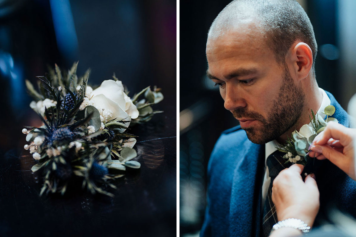 buttonhole by Quate and Co and being pinned onto groom's lapel
