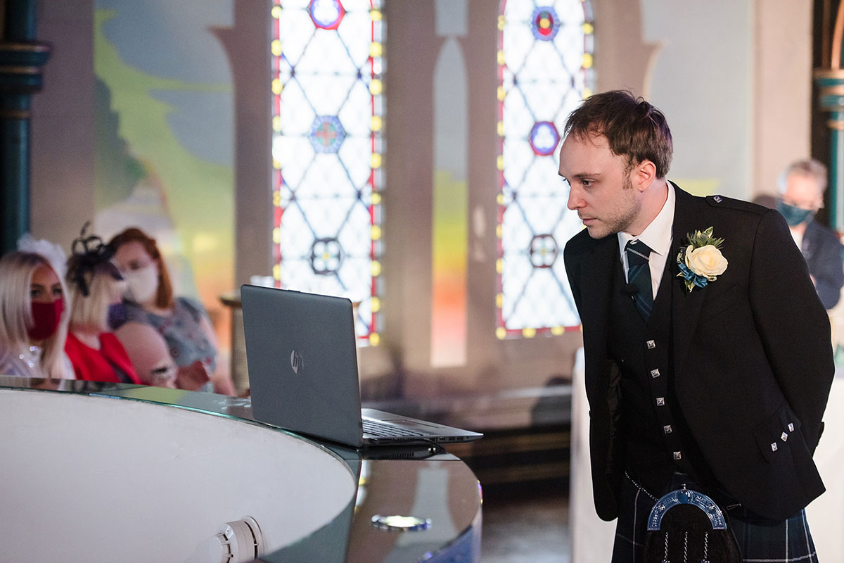 groom looking on laptop before start of live streamed wedding ceremony on mezzanine at Oran Mor