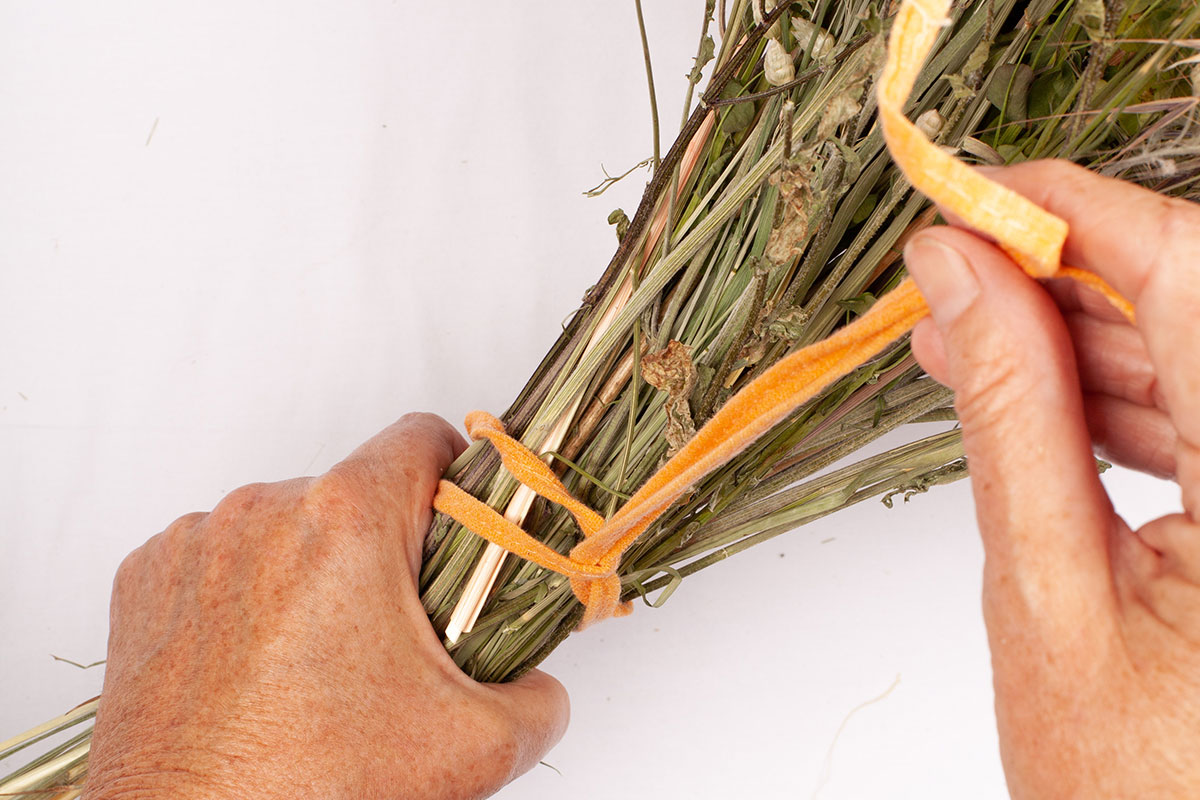 Hands tying twine round the stems of a dried flower bouquet