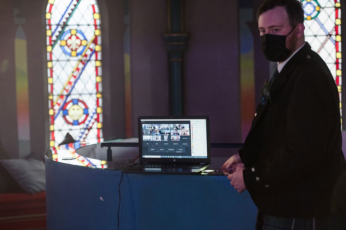 best man wearing mask looking at laptop during Zoom wedding ceremony at Oran Mor