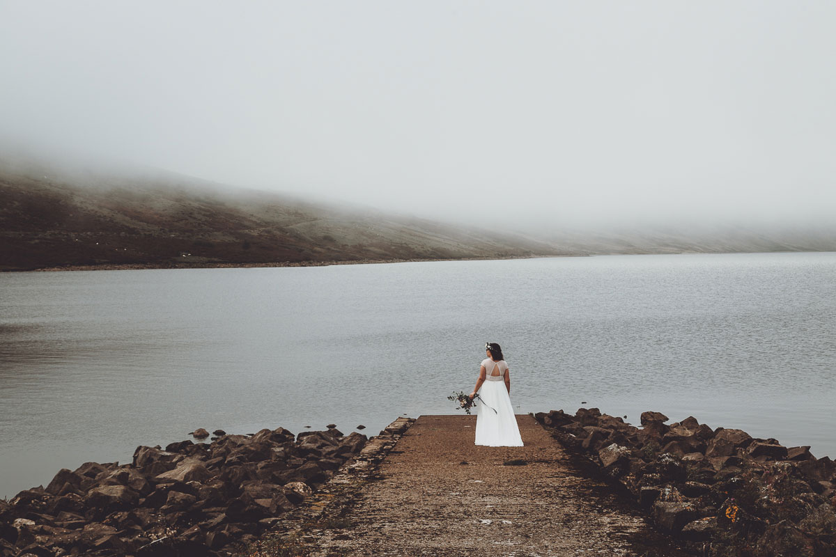 bride standing on jetty at Loch Turret Reservoir looking out onto mountains in Perthshire