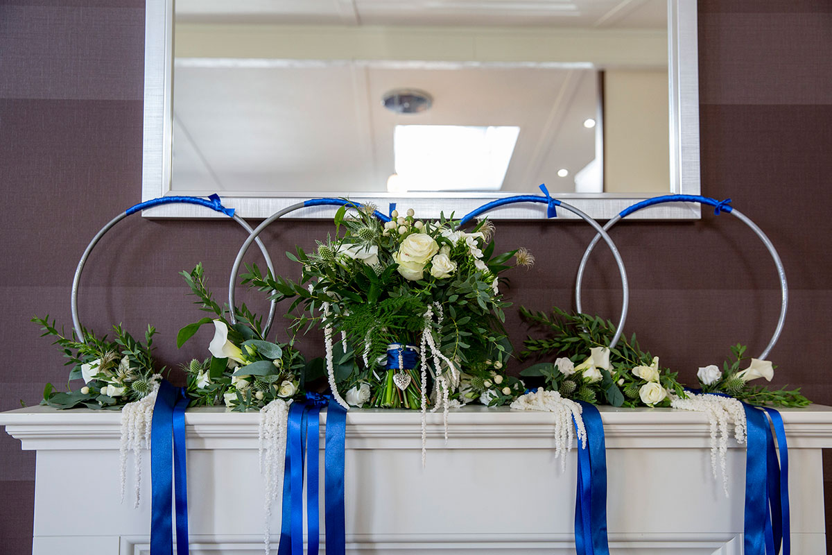 bridesmaid flower wedding hoops with royal blue ribbon and white roses sitting on mantelpiece