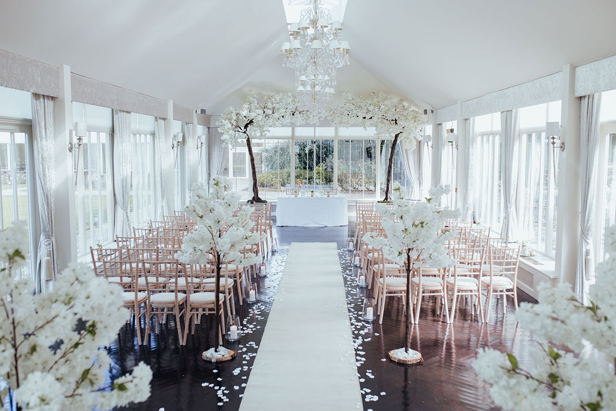 wedding ceremony set up in permanent marquee at Carlowrie Castle with flowers by Quate and Co