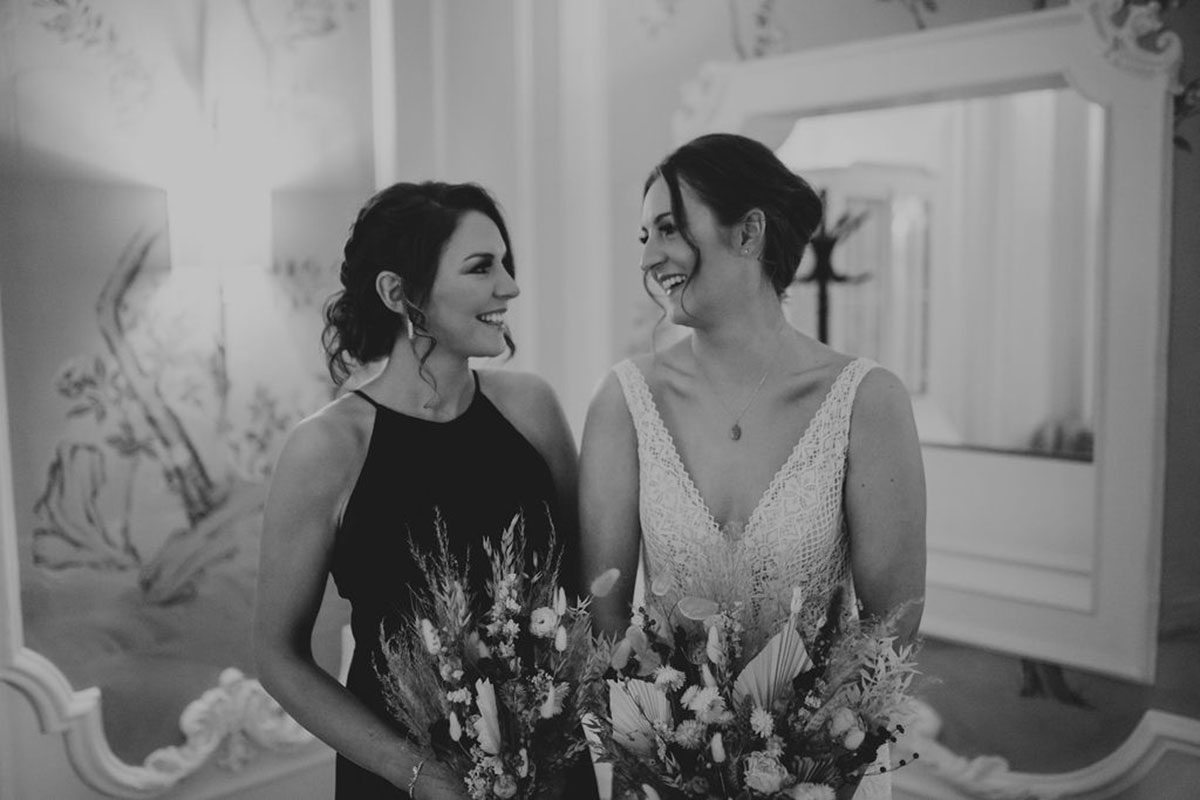 bride and bridesmaid smiling at each other before wedding ceremony at Waldorf Astoria Edinburgh