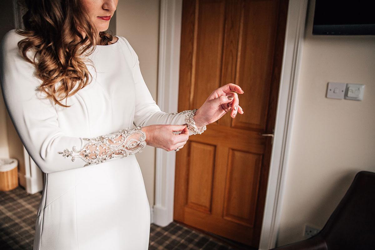 bride fastening lace cuff on Maggie Sottero wedding dress