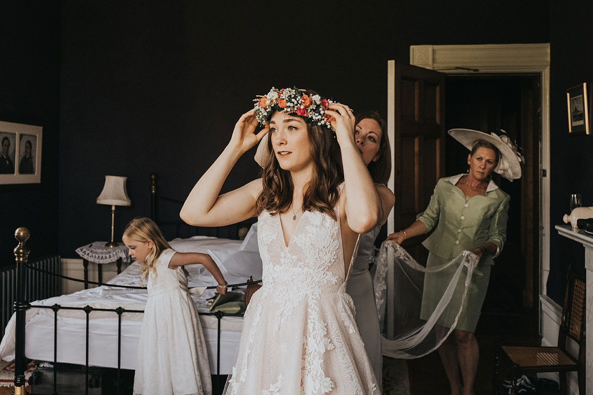 bride placing flower crown on head helped by bridesmaid and mother of the bride holding train