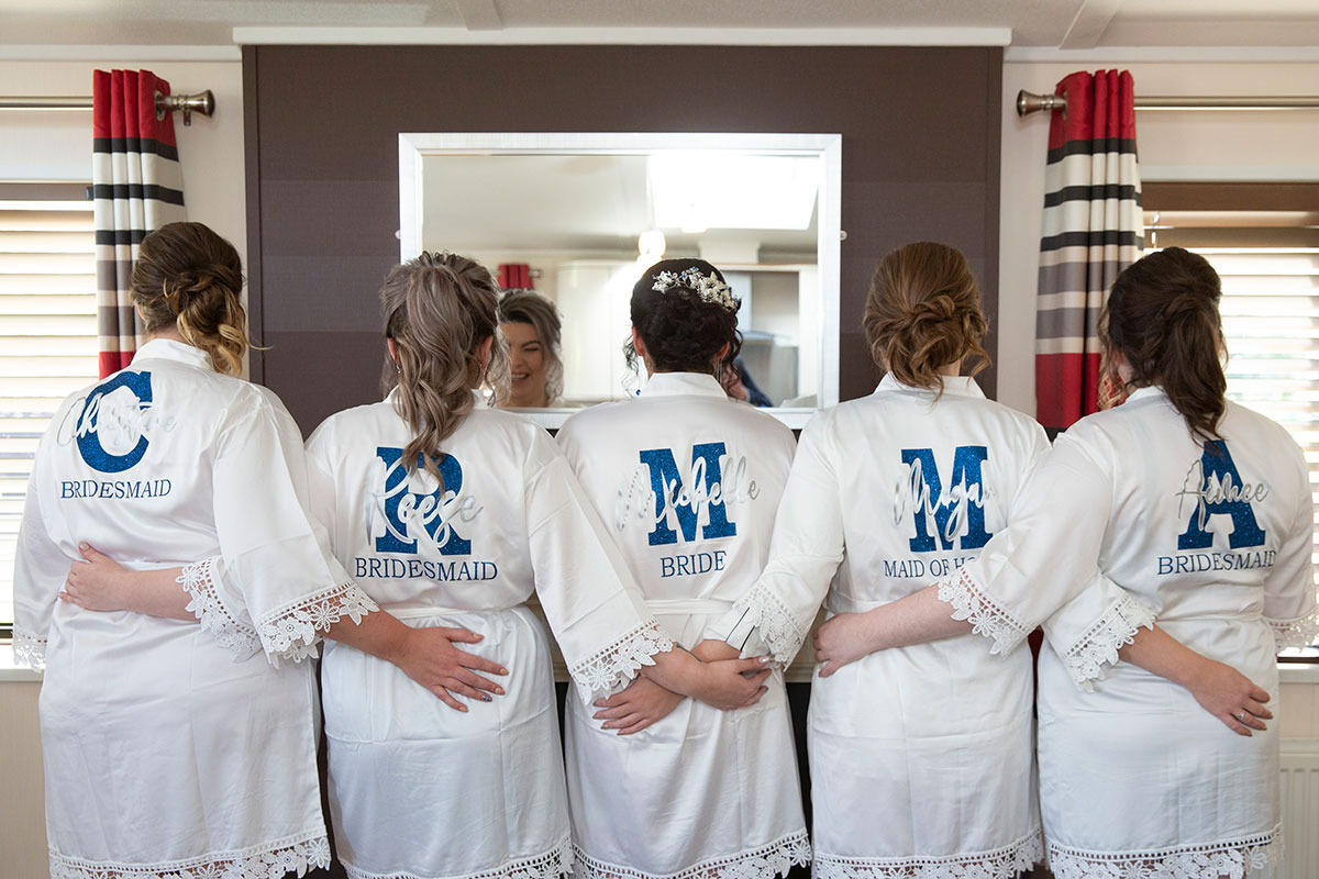 bridesmaids wearing personalised wedding dressing gowns with back to camera