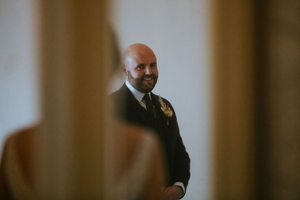 groom seeing bride for first time and smiling