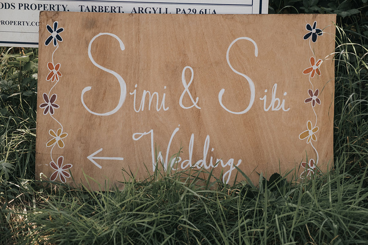 hand-painted wooden wedding sign with colourful flowers