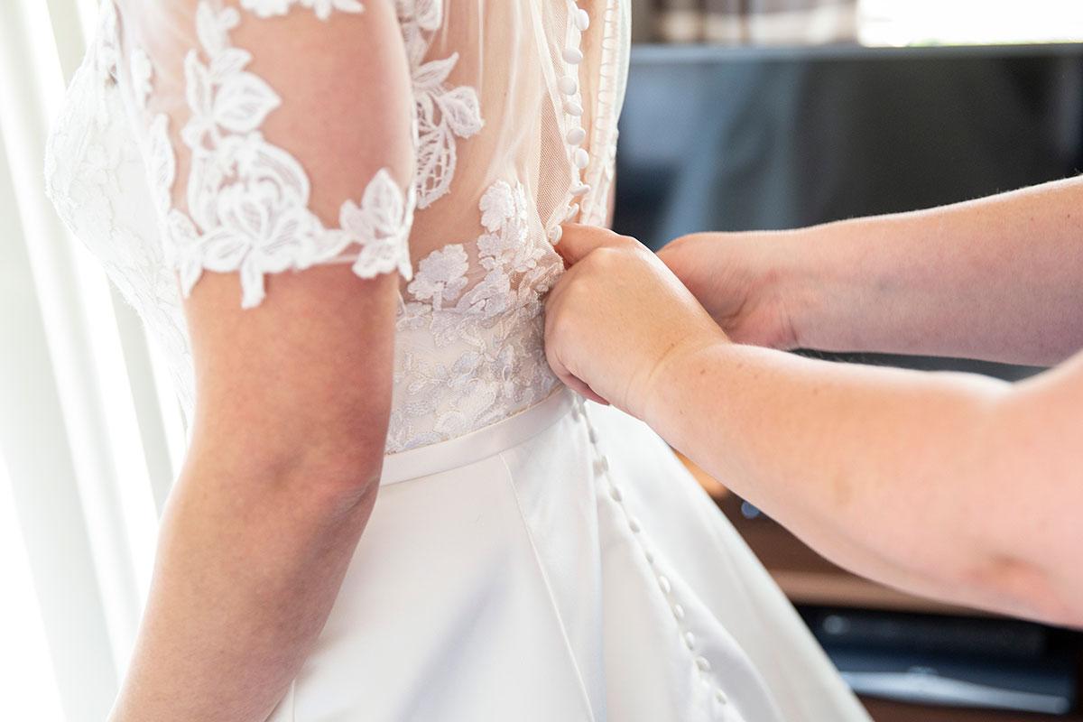 hands fastening buttons on bride's wedding dress