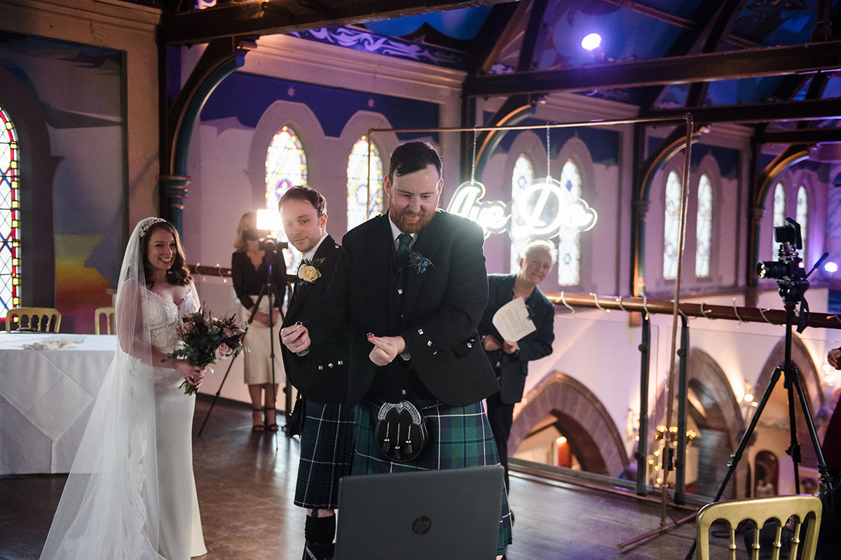 best man showing wedding rings to guests on Zoom during live streamed wedding ceremony at Oran Mor