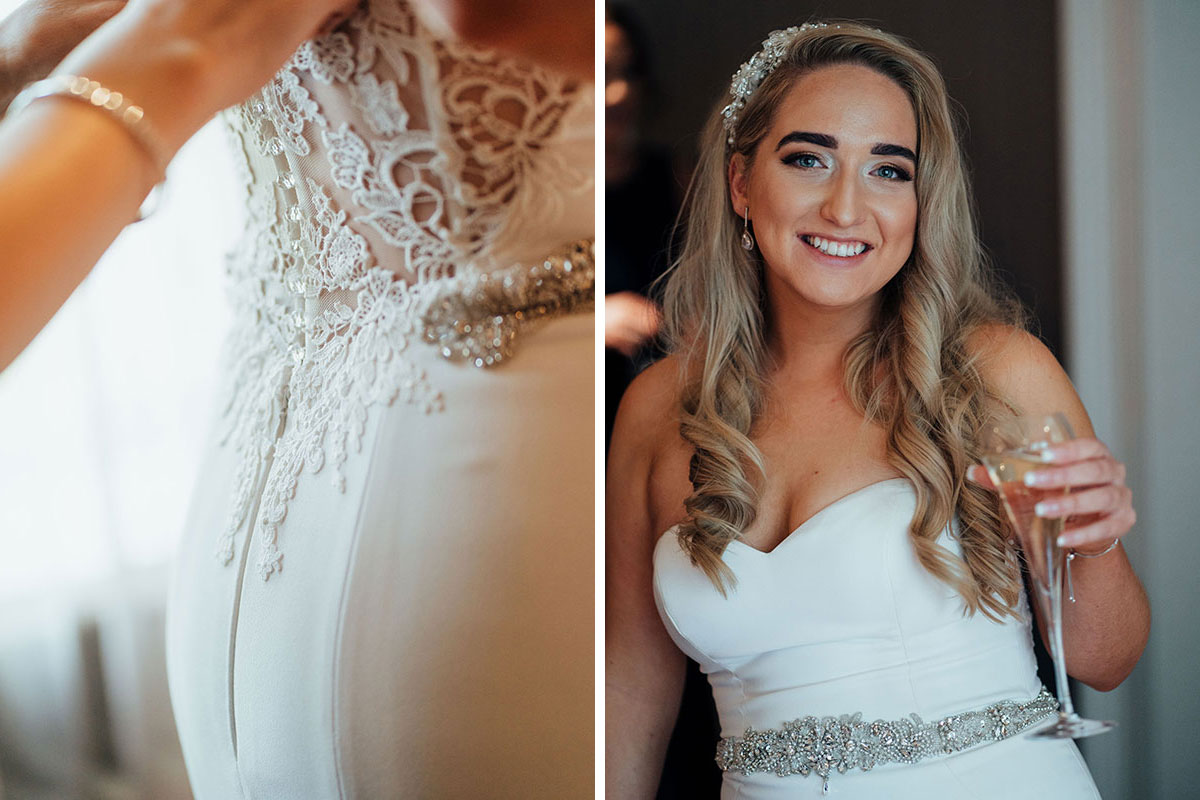 hand fastening button on back of lace wedding dress and bride carrying champagne flute and smiling at camera