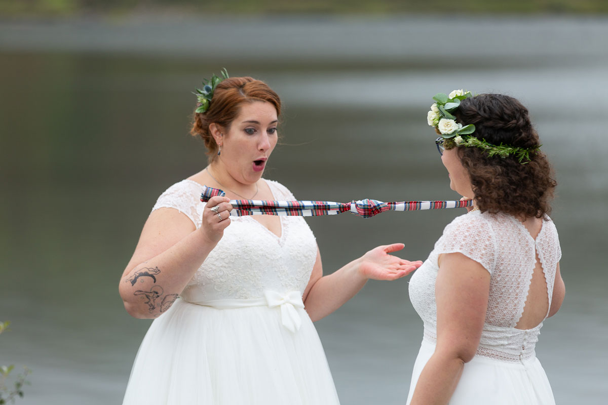 surprised brides tying tartan ribbon during outdoor lesbian wedding ceremony on shore of Loch Turret Reservoir in Perthshire