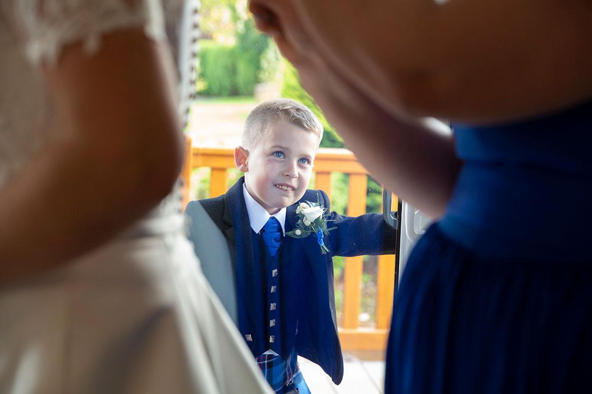 young boy smiling at mum and bridesmaid