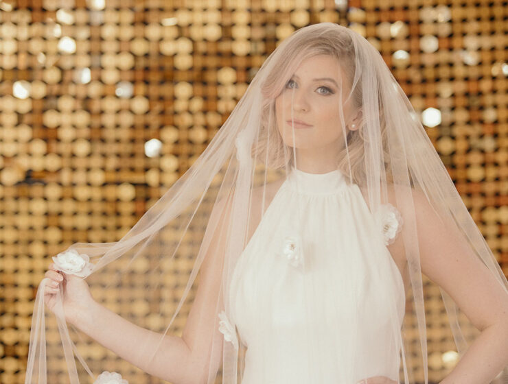 Blond female model on gold sparkly background wearing veil by Dillon King