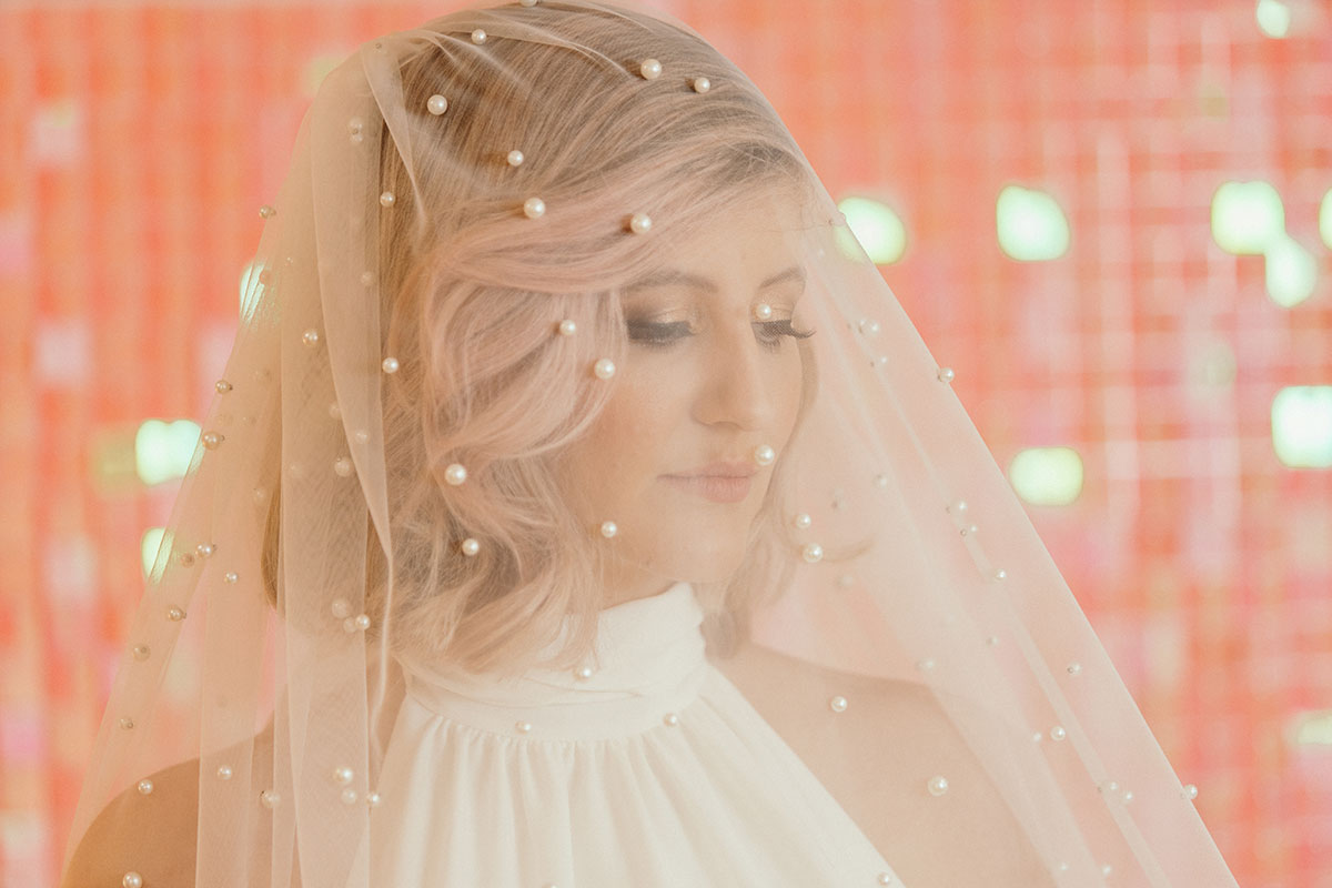 Blond female model on pink sparkly background wearing pearl veil by Dillon King