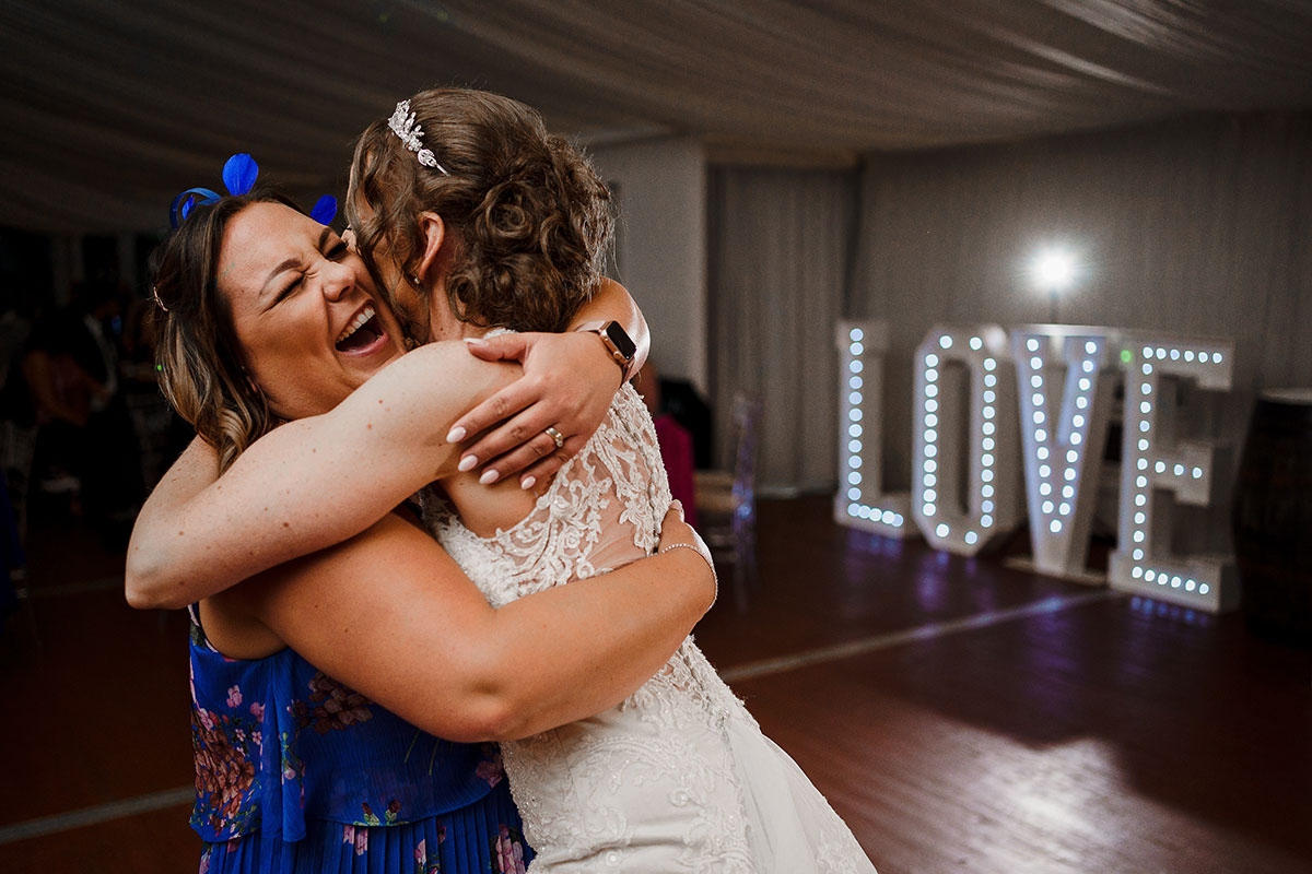 Bride hugging elated female wedding guest on dance floor at wedding with illuminated LOVE letters in background