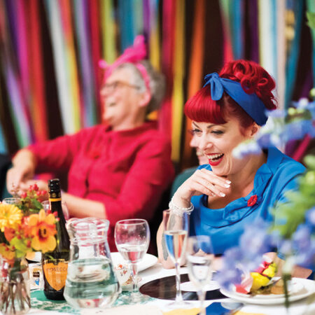 Female wedding guest wearing blue dress and headscarf sitting at a wedding table and laughing against a colourful ribbon backdrop with other male and female guests soft focus in background