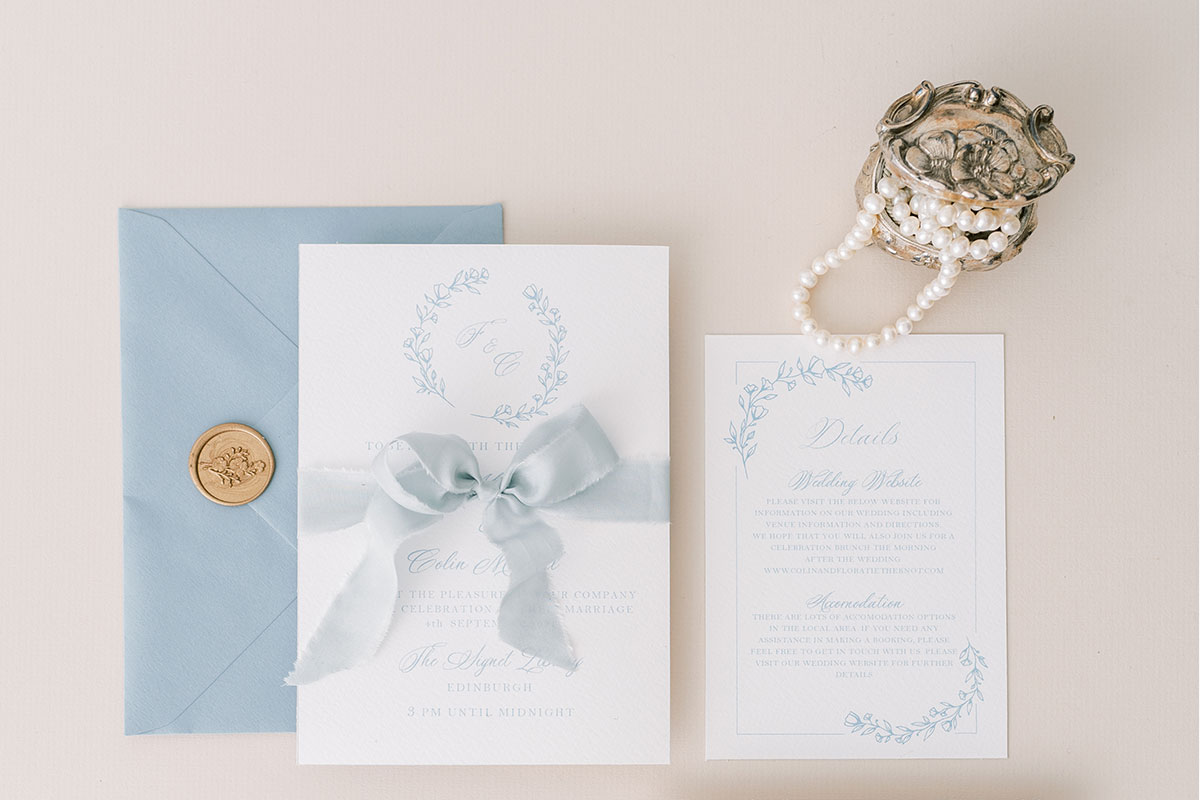 Ruby & Bloom Paper Co blue floral wedding stationery tied with ribbon