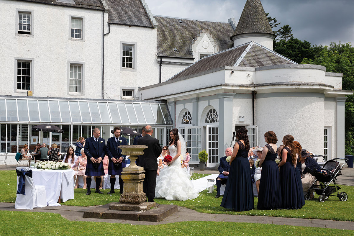 Wedding ceremony taking place on courtyard lawn at Barony Castle