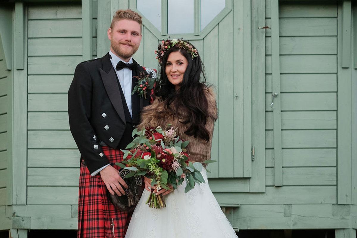 bride wearing faux fur stole with groom wearing red kilt at South Barlogan Farm wedding venue