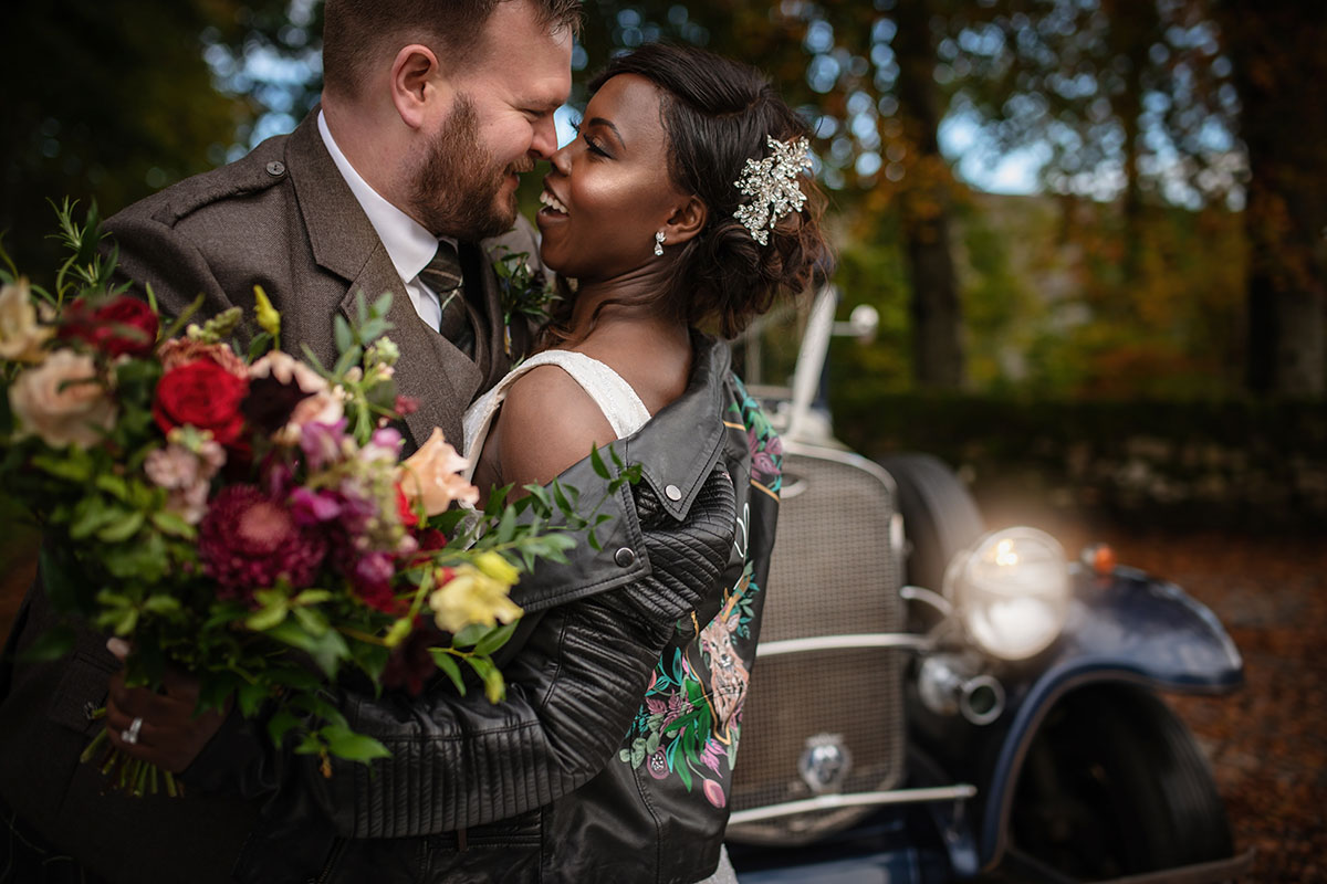bride wearing black painted leather jacket and carrying bouquet by Kim Dalglish kissing groom in front of wedding car by Silver City Wedding Cars
