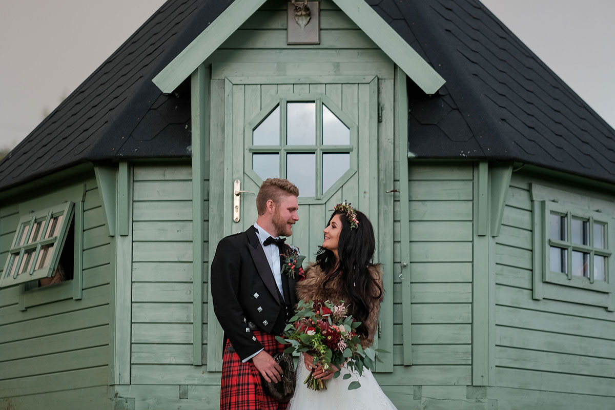 bride wearing faux fur stole with groom wearing red kilt at South Barlogan Farm outside green clapboard glamping hut