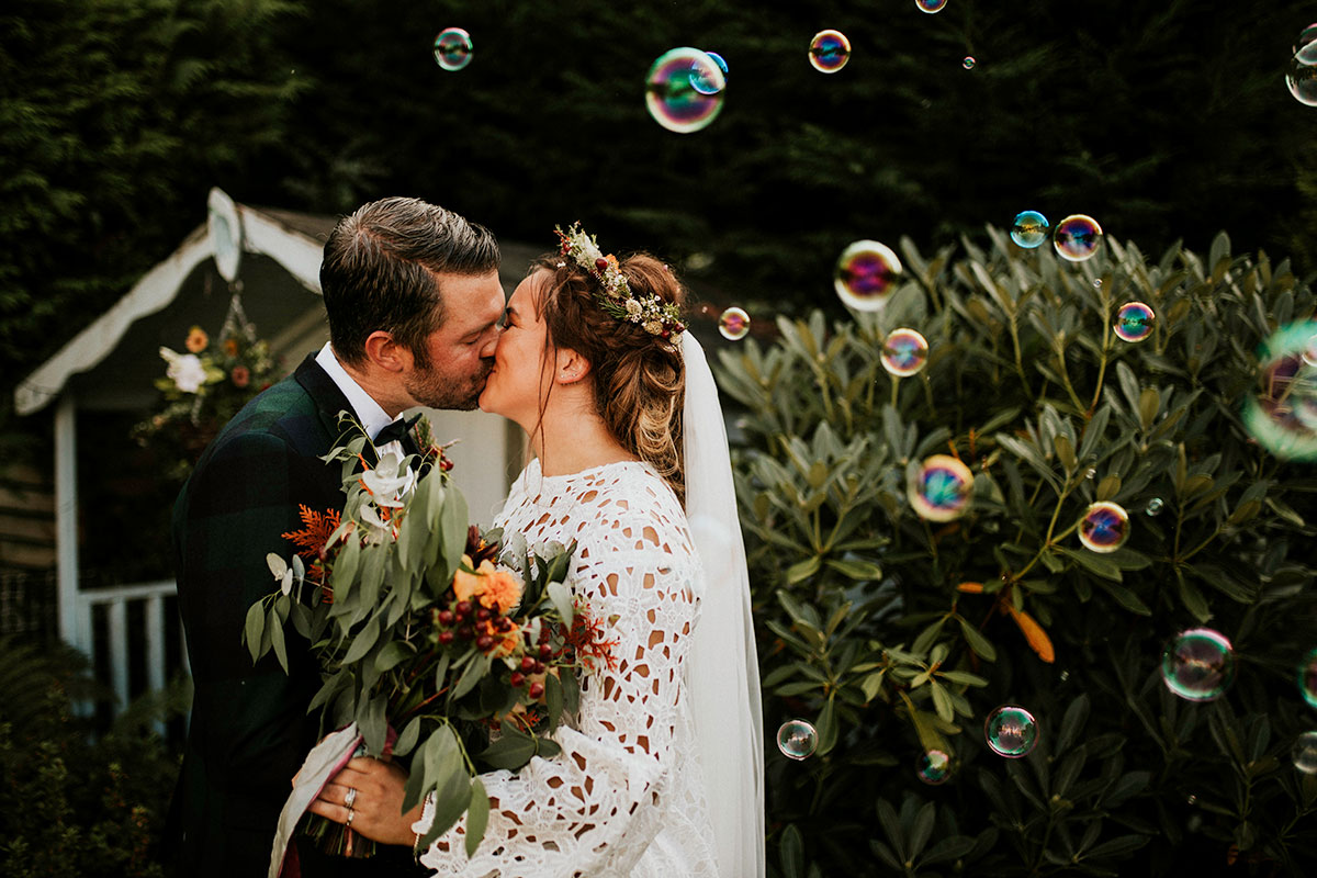 bride wearing white boohoo dress and groom wearing ASOS suit kissing at their Edinburgh garden wedding surrounded by bubbles