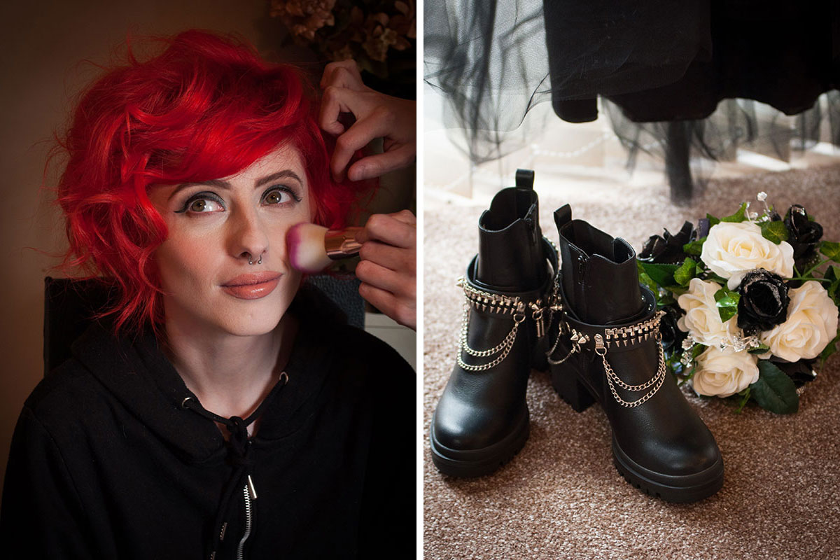 red haired bride wearing black and getting makeup done and black biker boots with chain sitting on floor next to wedding bouquet