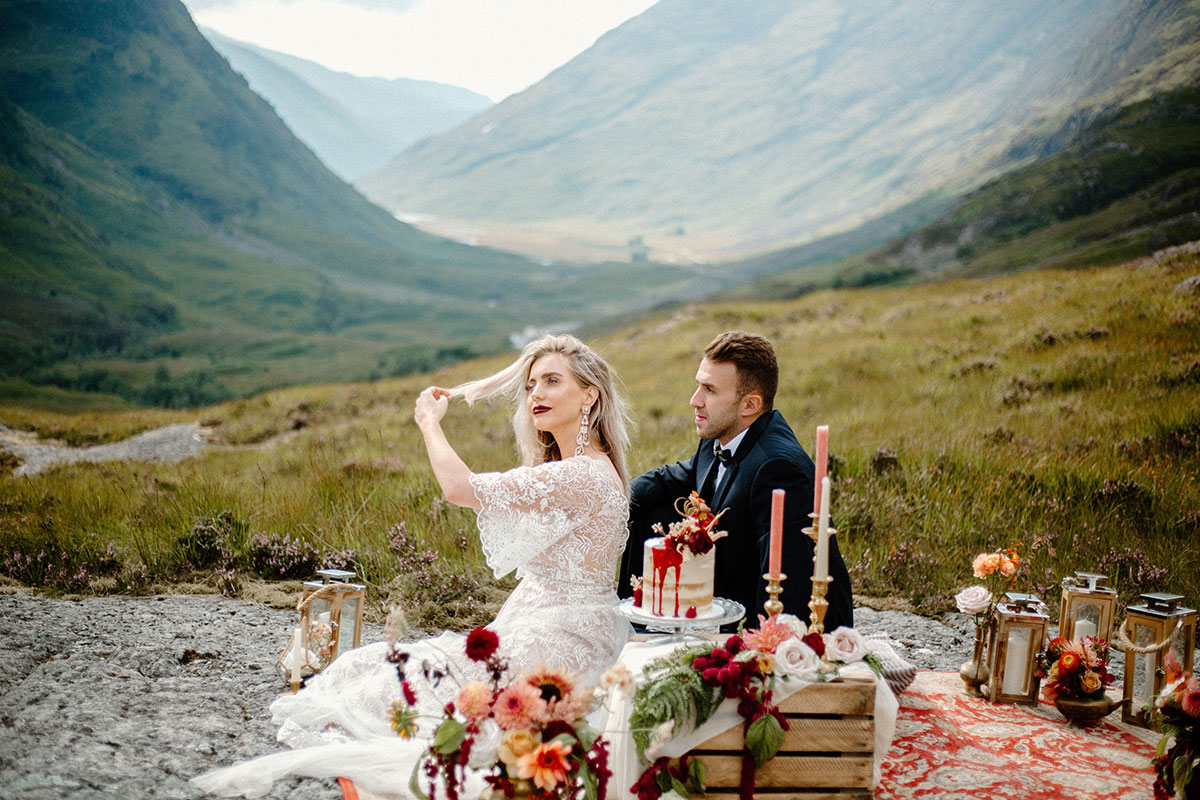 bride and groom sitting on persian rug styled with candles cake crate and flowers in Glen Coe