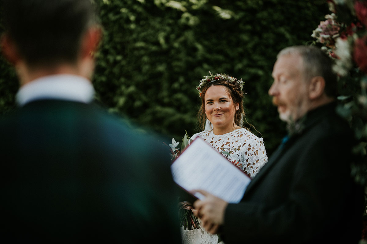 bride smiling at groom while male wedding celebrant leads the ceremony in an Edinburgh back garden