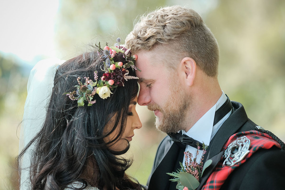 dark-haired bride wearing flower crown with head together with groom wearing red tartan fly plaid