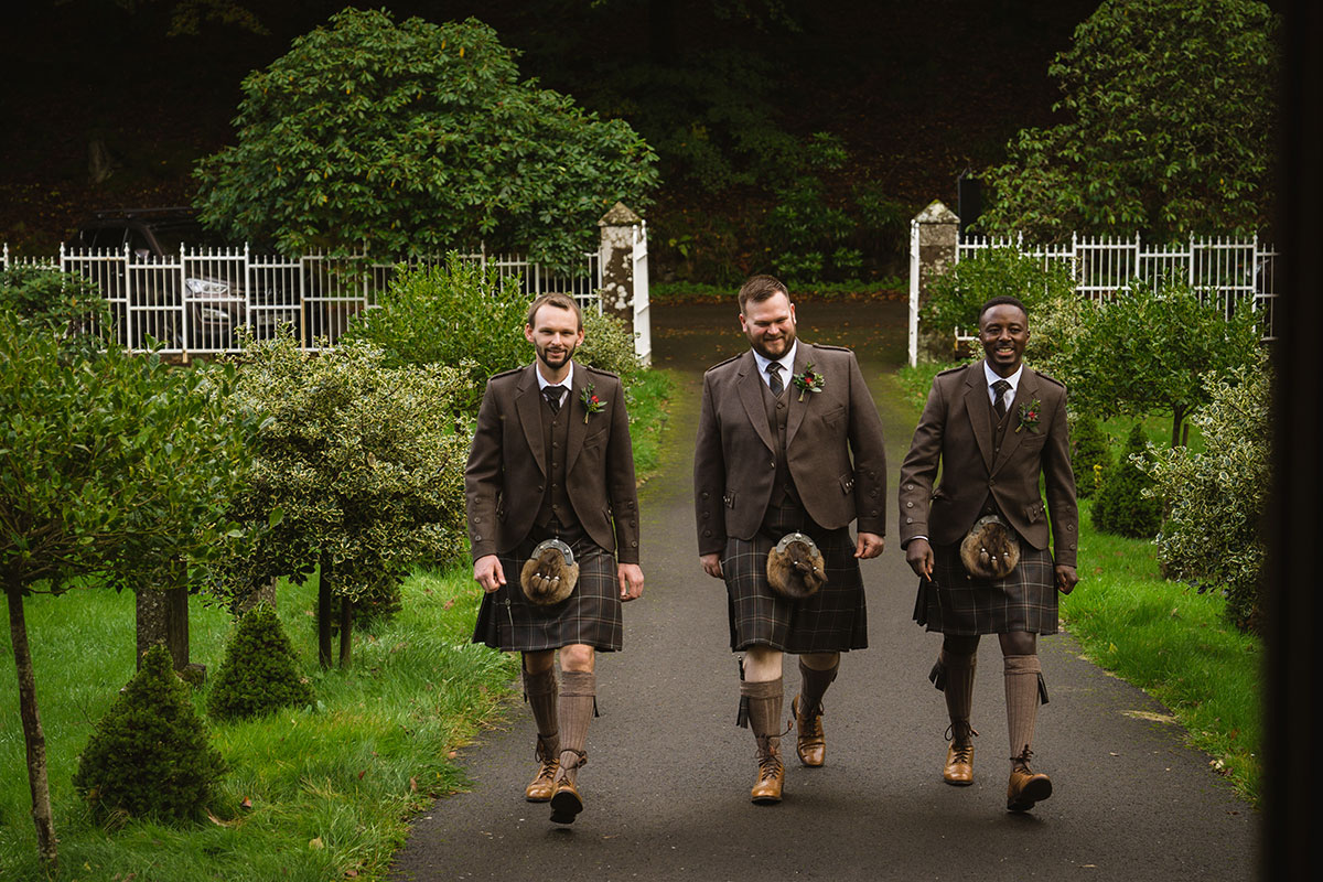 groom and two ushers wearing kilts walking towards St Palladius Church at Drumtochty Castle
