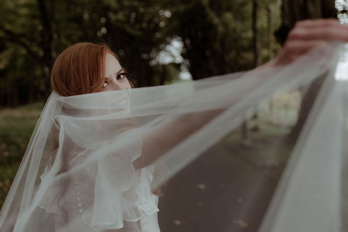 red haired bride smiling and looking over shoulder into camera holding veil up close