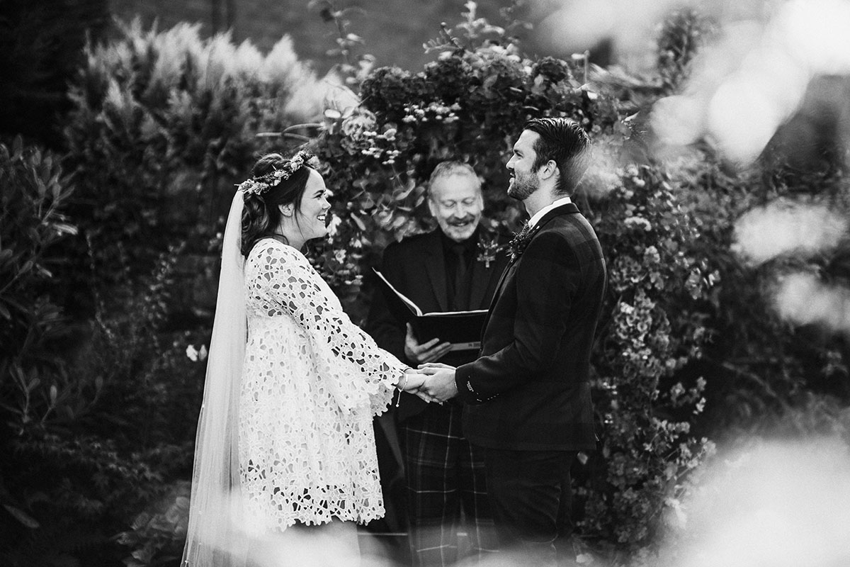 black and white image of a bride and groom holding hands while celebrant reads vows at Edinbugh back garden wedding