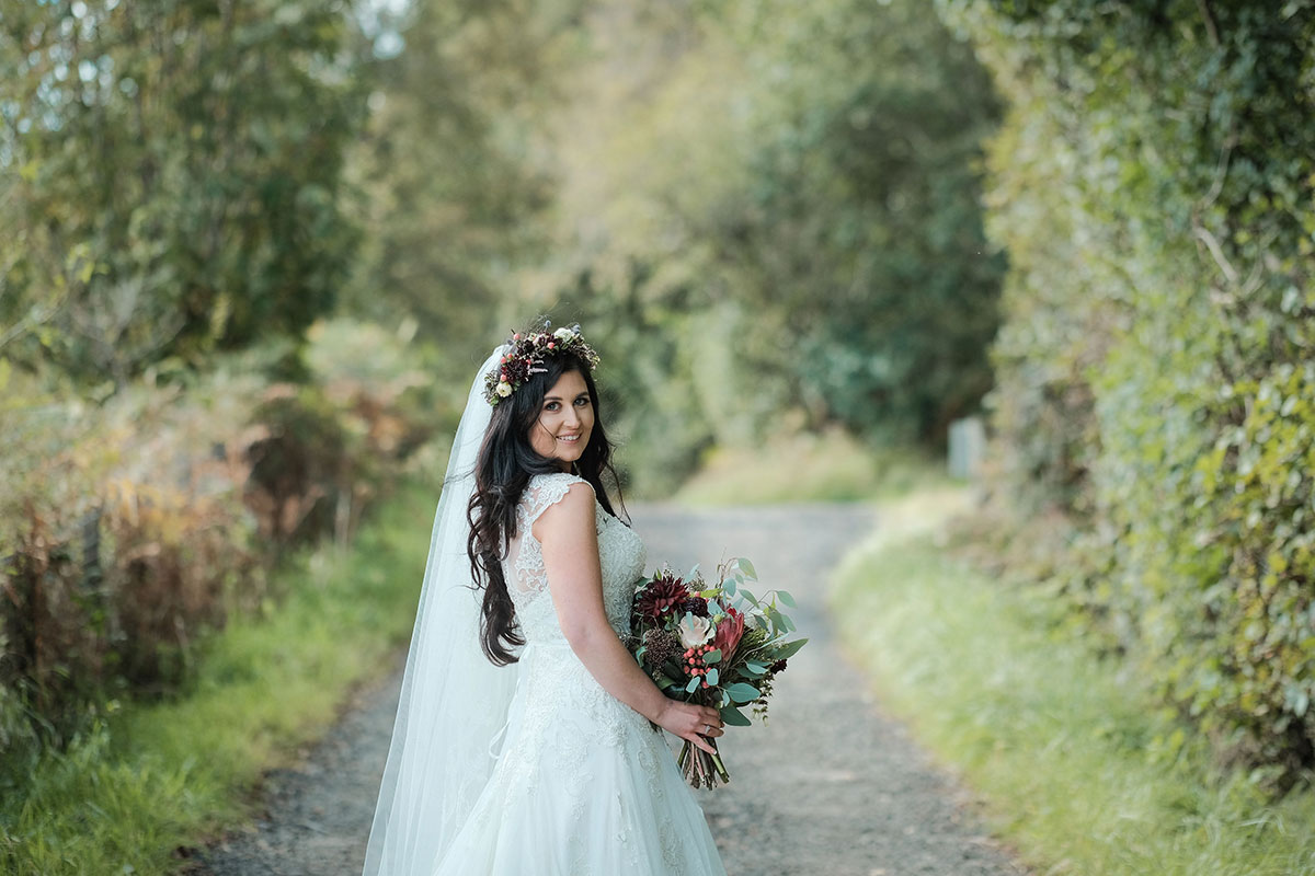 bride walking down country road in Renfrewshire looking back over shoulder carrying a bouquet and wearing flower crown by Posies and Pots
