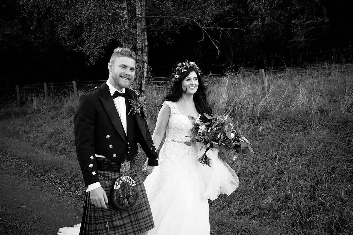 black and white image of bride and groom walking hand in hand along rural road at South Barlogan Farm