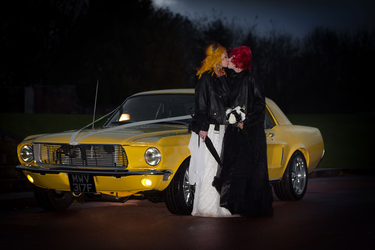 yellow mustang from Glasgow American Car Club with two brides posing at nighttime McDonalds Halloween wedding