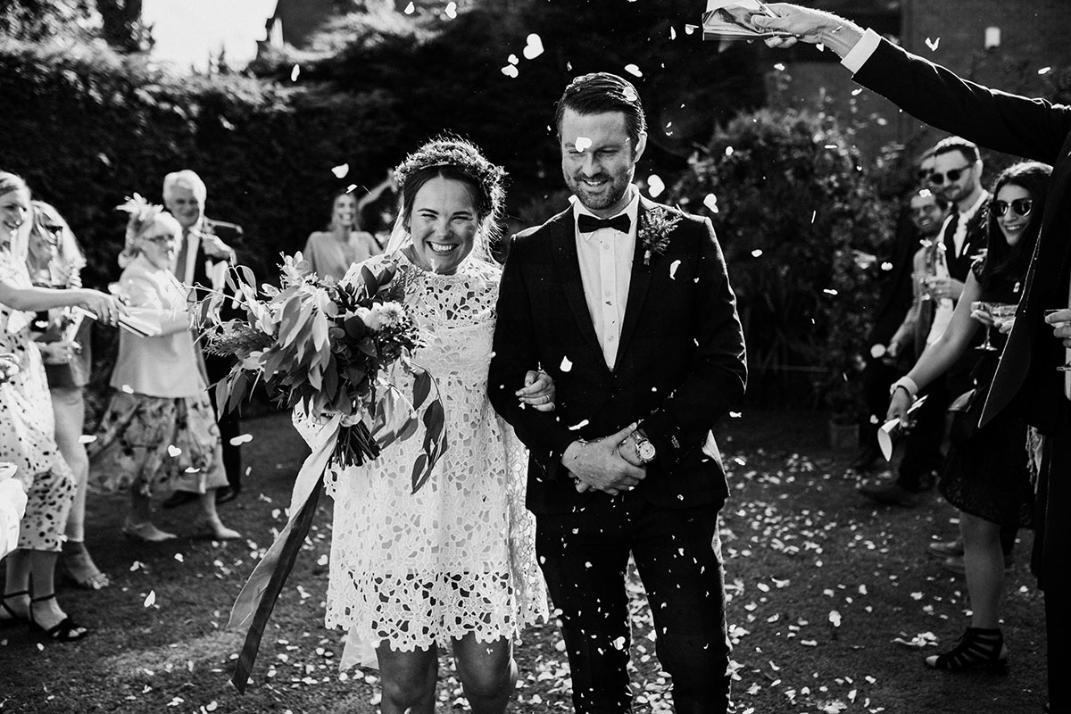 black and white image of bride and groom being showered in confetti at relaxed Covid Edinburgh garden wedding ceremony