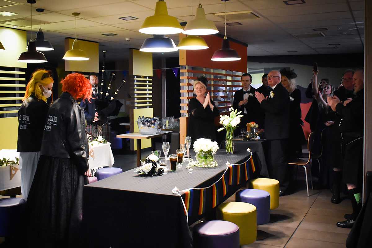 two brides having wedding dinner at McDonalds Halloween wedding with family looking on