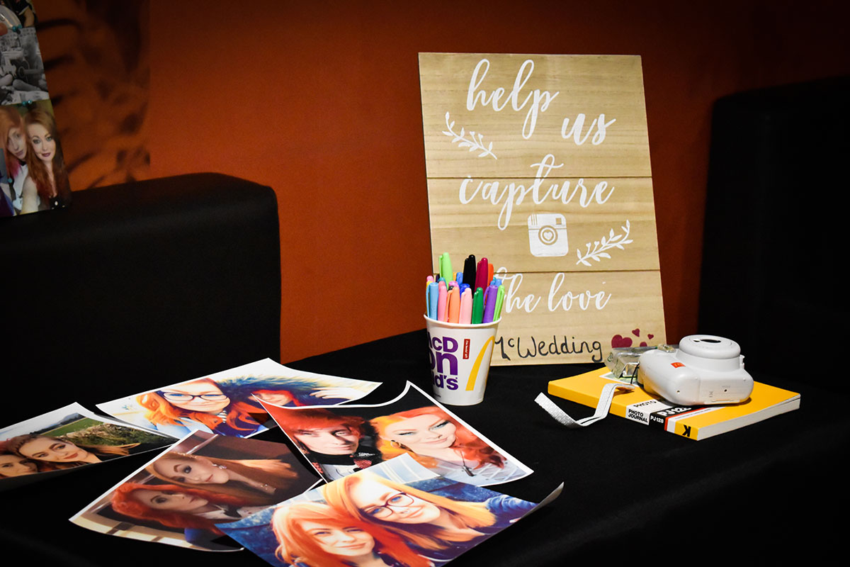 DIY photo booth table at McDonalds Halloween wedding with print outs of photos of two brides on table