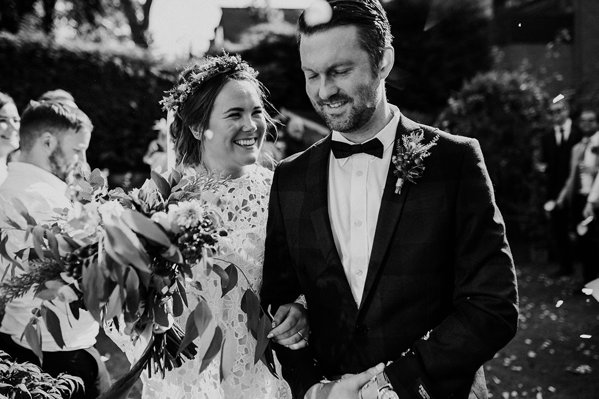black and white image of bride and groom smiling at relaxed Covid Edinburgh garden wedding ceremony